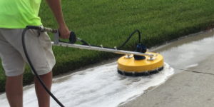 Surface cleaning a driveway by Suncoast Roof Cleaning in Sarasota